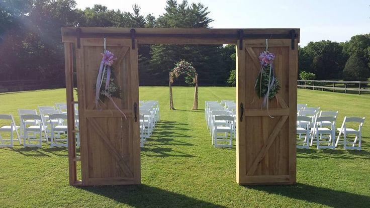Barn door wedding aisle entrance with rustic ceremony arch.