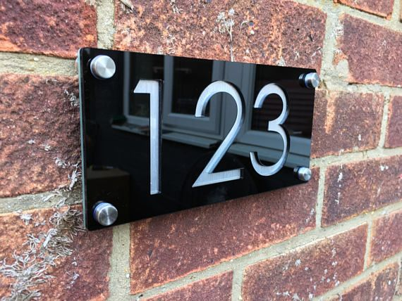 Modern Door Number and street Plaque Please leave the door number and street name you require in message to seller (payment notes) during purchase or message us the details through etsy. 5mm gloss Black front plaque 3mm aluminium effect backing panel Approx 300mm/140mm Fast and free delivery Four stainless steel stand offs supplied Century gothic numbers and street name recessed