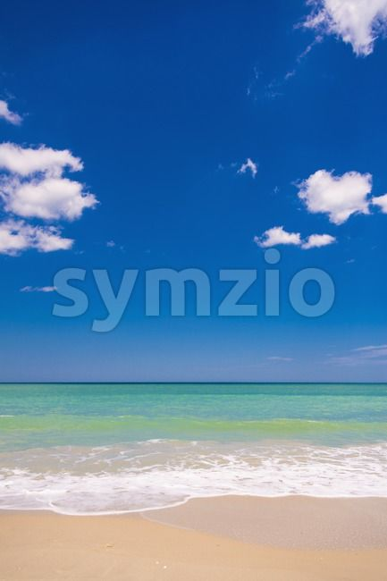 Stock photo of Beautiful sandy beach from $1.99. Beach scene with blue sky and few white puffy clouds,...