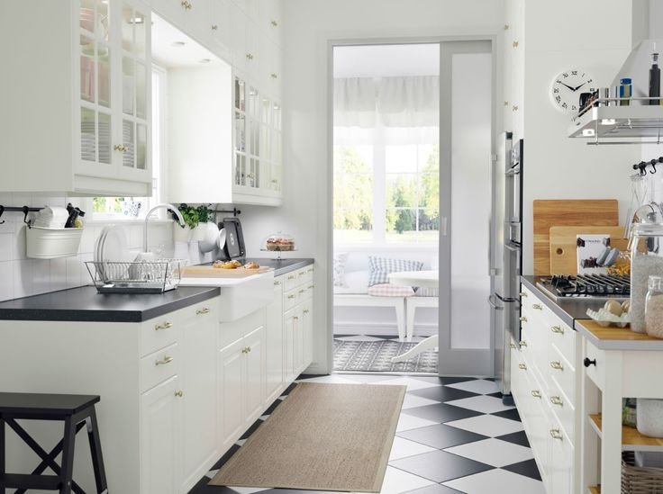 A small country kitchen with white drawers, doors and black countertops. Love that the cabinetry goes all the way to the ceiling. <3