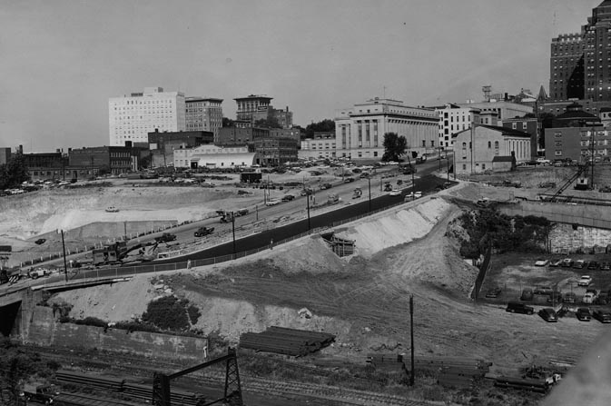 View of Toll Road Construction From Marshall Street Viaduct by Tom Netherwood; Richmond Newspapers, Inc. - May 25, 1957  Black and white photograph of construction of the Richmond-Petersburg Turnpike; image shows downtown Richmond from the Marshall Street viaduct; a temporary by-pass at Broad Street crosses the center of the photo; numerous office buildings and part of the Medical College of Virginia campus are visible in the background; construction equipment lines the by-pass.
