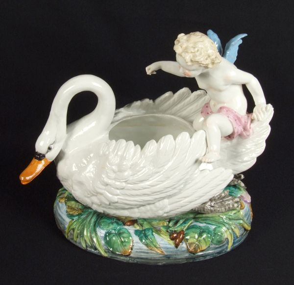 MEISSEN PUTTI AND SWAN BOWL. Meissen porcelain bowl on oval base, putti seated on swan form bowl, swan on polychrome pond base. Marked: Blue underglazed crossed swords mark, with star and dot