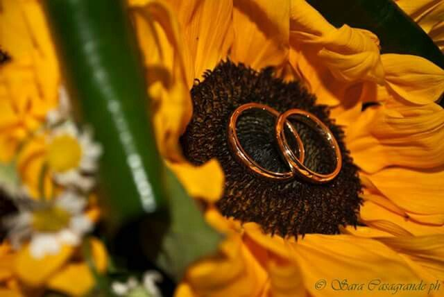 Our wedding rings on my bouquet of sunflowers