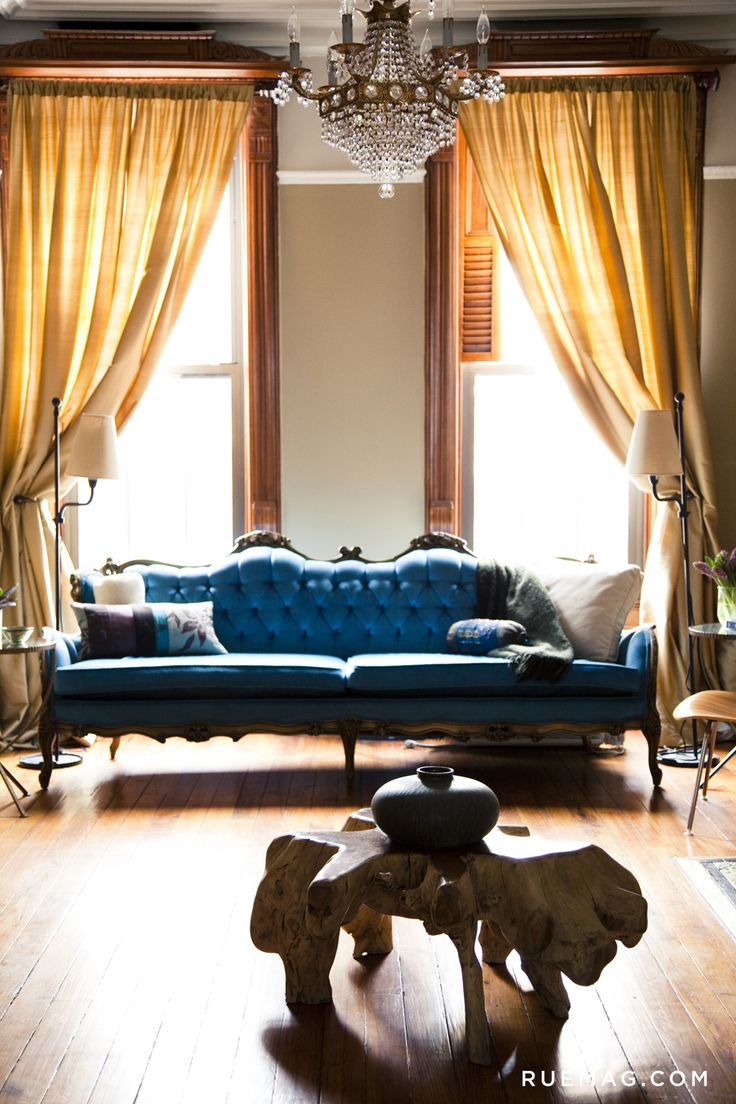Antique re-upholstered sofa, combined with chandelier, beautiful hardwood  and buttery yellow curtains.