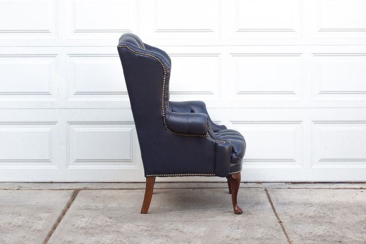 """We have another handsome vintage leather club chair in the shop. This piece has a classic wingback frame with button tufting and nailhead trim everywhere and cabriole or queen anne style legs. Its navy leather upholstery is in great shape with a nice distressed finish (especially on the seat) from years of natural use. Its a very comfortable chair, great for watching tv or reading a book.  Dimensions: 31"""" Deep 32"""" Wide 43"""" Tall 21"""" Seat Depth"""