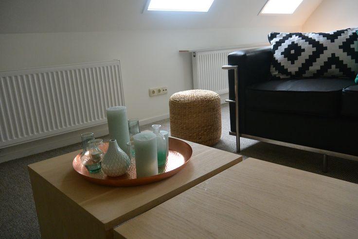 Appartement 1. Tafels en poef (Leenbakker), kussen (Ikea), kaarsen en schaal (Xenos), vaasjes (Action), bank (privébezit verhuurder)