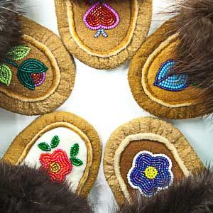 One of a kind, hand beaded moosehide moccasins crafted by the skilled Dene artisans in Fort Liard, Northwest Territories, Canada.Each pair of slippers takes dozens of hours to smoke and cut the moosehide and then hand bead the intricate design. The slipper is then accented with traditionally trapped beaver fur. Great to wear around the house and to keep your feet warm on a chilly day.We offer numerous different sizes of moccasins for men and women. Sized from infants to adults.Prices range…