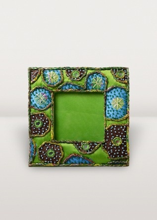 A celebration of green! This ornate photo frame is ornamented with intricate applique beadwork, mirrors and recycled plastic cord. Earth friendly and Fair Trade.