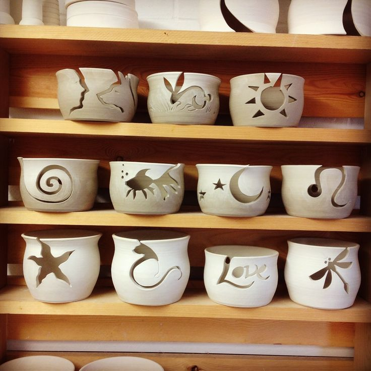11 new Yarn Bowls with cut out designs drying on the shelf before their first firing.
