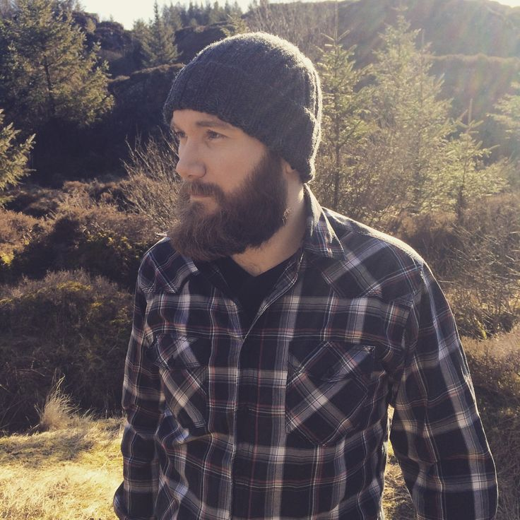 The look of a true lumberjack. Knitted hat, plaided shirt and a brown beard.