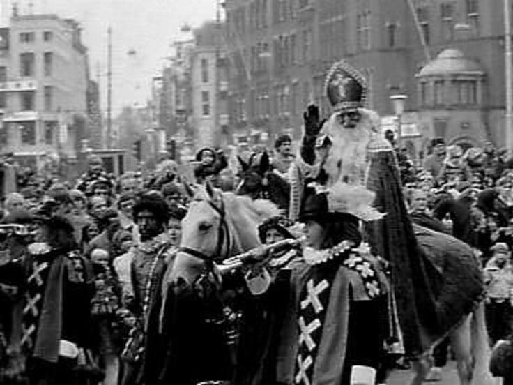 Intocht Sinterklaas Amsterdam. Op de foto: Sinterklaas, Zwarte Piet en 2 paardenknechten. Ca. ?