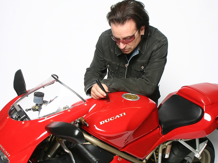 A Ducati 916 owned and signed by U2 frontman Bono will being going up for auction at the NEC Motorcycle Show to raise money for motorcycle charity Riders for Health.    The Ducati 916 was formerly owned by the late INXS singer Michael Hutchence, and Bono's U2 bandmate Adam Clayton.