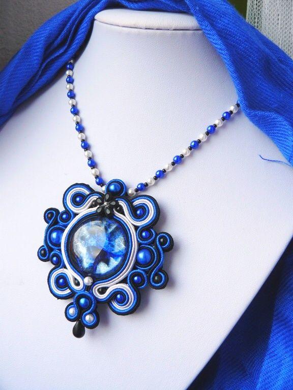 Bouřka Exkluzivní a neopakovatelný přívěsek vytvořený časově náročnou technikou sutaškování. Střed přívěsku je tvořen sklěněného, ručně malovaného kabošonu z dílnyLileas materiálv modročernostříbrné barvě. Na výrobu byly dále použity textilní prýmky - sutašky v čtyřech barvách -modré, černé bílé a šedé, skleněné perličky v bílé, černé ...