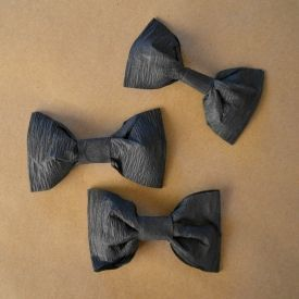 How to make cute bowties out of just a few cents worth of crepe paper.  Perfect for wedding decor or photo props