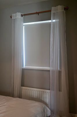 Copper and White Window Dressing. The lightweight curtains help to create a romantic look to the room, while blinds help to block out the light. The curtain pole has been spray painted copper to change the look on a low budget.