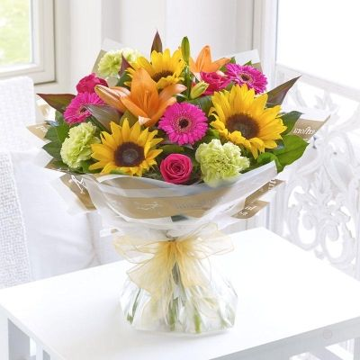 Sunflower Mixed Hand tied  Send them a gift of summer sunshine with this dazzling hand-tied bouquet. The stars of this design are the magnificent sunflowers, and they look fantastic partnered with bright orange lilies and hot pink tones. This is a gift to really brighten their day and their home.
