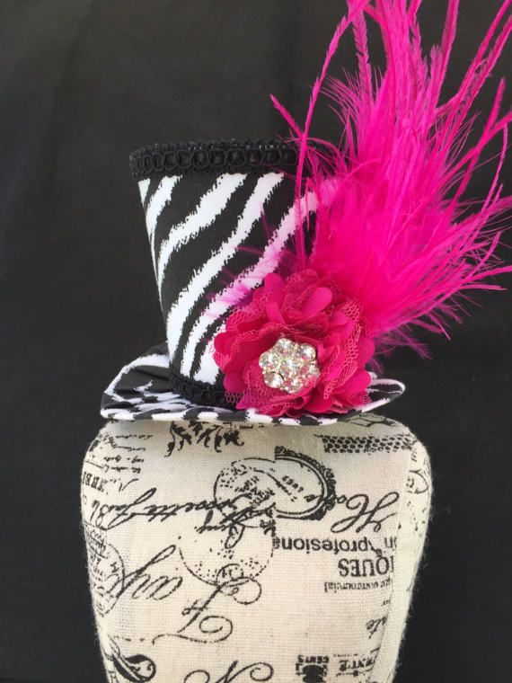 This adorable mini top hat is completely handmade and one of a kind. This would make great accessory for a wedding, bridal shower, bachelorette party or photo prop.  The hat is approximately 3 inches tall and brim has approximately 4 inch diameter. The mini top hat is covered in a black and white cotton fabric with a zebra stripe design. The trim is black. The hat is adorned with a pink satin flower with a crystal button and pink ostrich feathers to complete this adorable look!  This hat can…