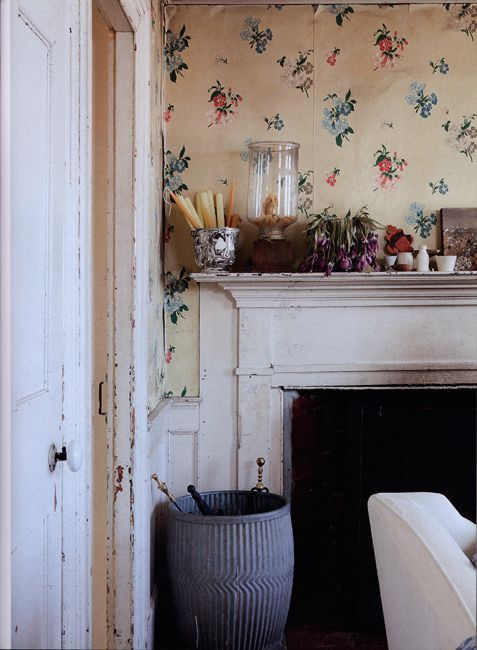 Floral wallpaper and old fireplace