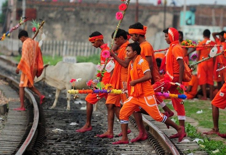 <p>Indian Hindu devotees of the deity Shiva cross a railway track at Daraganj railway station as they arrive to collect water from the Ganges river for their ritualistic walk towards Varanasi during the holy month of Shravan, in Allahabad on July 28, 2016. Shravan is considered the holiest month in the Hindu calendar with many religious festivals and ceremonies. </p>