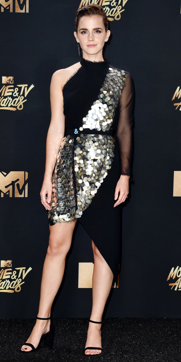 Look of the Day - Emma Watson: The star wore a glittering sequin and black mesh dress, strappy heels, and an edgy asymmetric earrings to the 2017 MTV Movie & TV Awards.