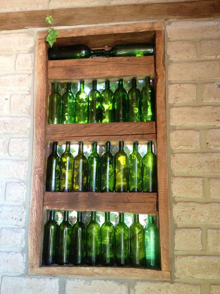 Ventana rustica hecha con madera y botellas de vino en casa de adobe en region de Villa de Leyva Colombia