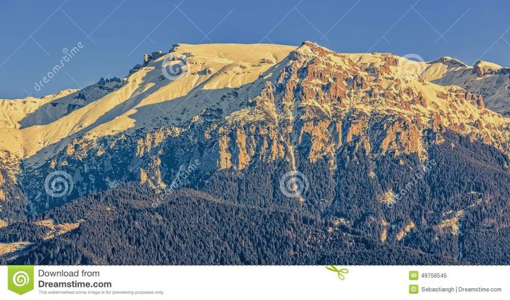 Close view of sunlit Bucegi mountains ridge with steep slopes covered by snow at sunset, Romania.