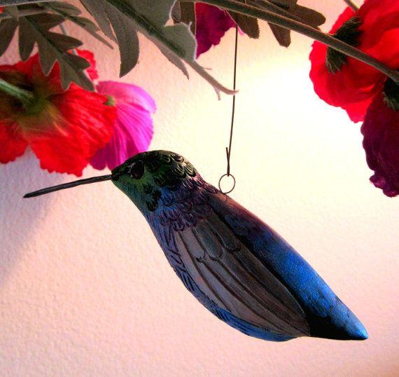 Glinsterende en goed verlicht, zal deze hummingbird in levendige blues en Groenen toevoegen van schoonheid en vraag me af bij u thuis. Hang hem van een kleine oog van de schroef in uw venster of van een plank - hij is zeker uw aandacht te vangen wanneer u voorbij.  Voorzichtig gebeuren van zijn veren en delicate hand schilderij in meerdere kleuren maken zijn levensechte kwaliteiten.  Elke vogel in mijn ecoflock is hand gevormd uit witte klei waardoor ze een van een soort en afgewerkt door…