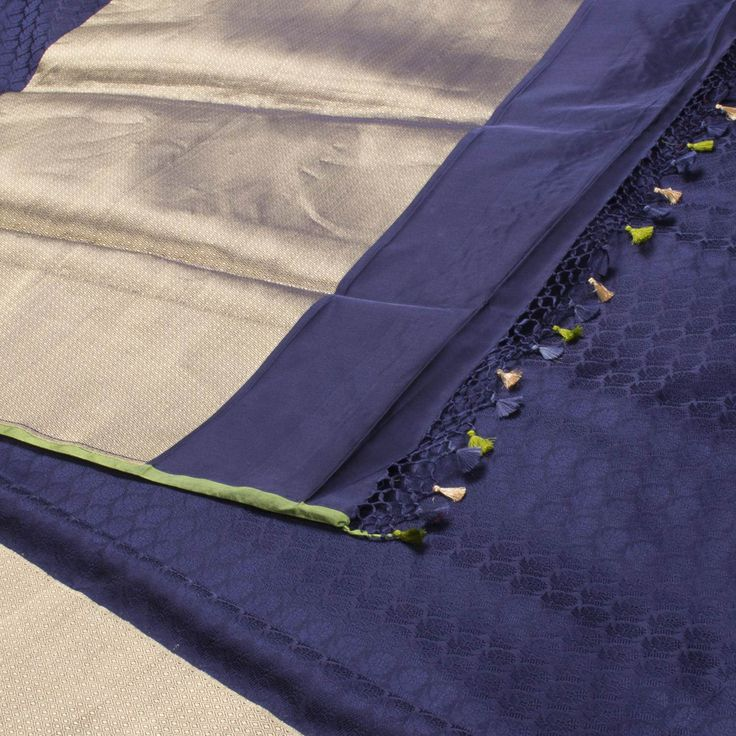 """The """"#Navy #Blue"""" #handwoven #Banarasi #Satin #Silk #Sari from Shivangi Kasliwal is woven with floral bhutas all over the body that is set off by a gold zari banarasi border and pallu. The border is repeated on the green blouse with paisley motifs."""