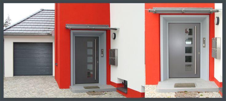 Die graue, solide Haustüre mit quadratischen Lichtausschnitten vor dem roten Hintergrund, gibt dem Mehrfamilienhaus einen unverwechselbaren Charakter.