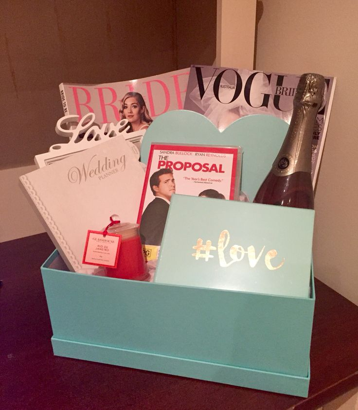 "This is the engagement gift box for one of my best friends Tai! This gift box includes: - 2x bridal magazines - 1x Jacob's Creek sparkling rose wine - 1x wooden heart - 1x LOVE photo frame - 1x wedding planner - 1x ""The proposal"" movie - 1x Glasshouse fragrance candle (scent: Rio De Janeiro) - 1x #Love photo albumn"