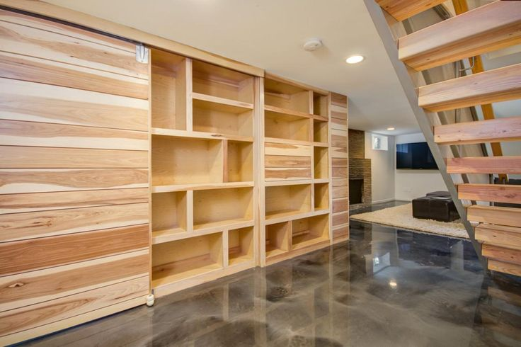 A custom sliding barn door wall system features plenty of shelf space for storage in this urban basement. A hidden built-in bar allows for adult entertaining.