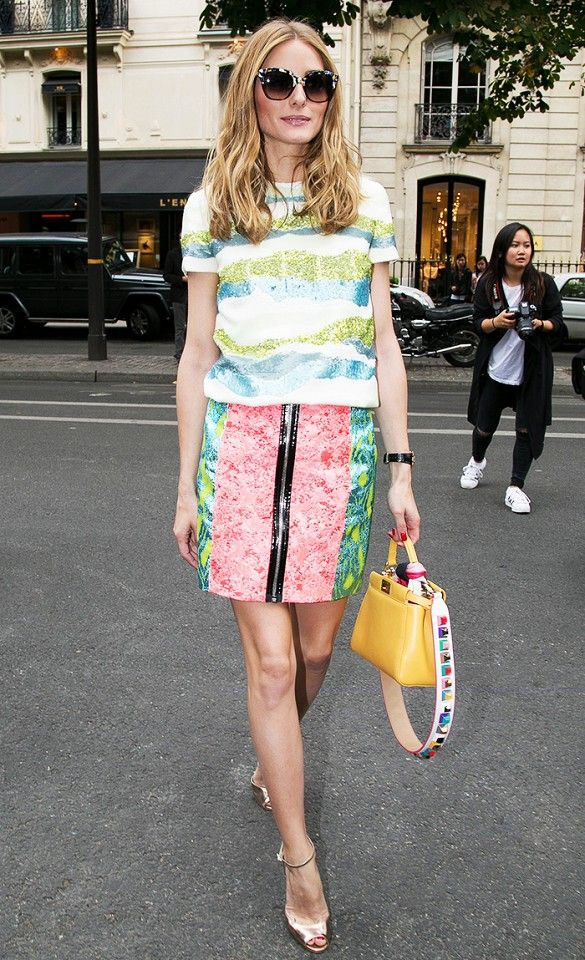 Olivia Palermo wears a sequin striped top, pink and green skirt, metallic heels and a yellow bag.