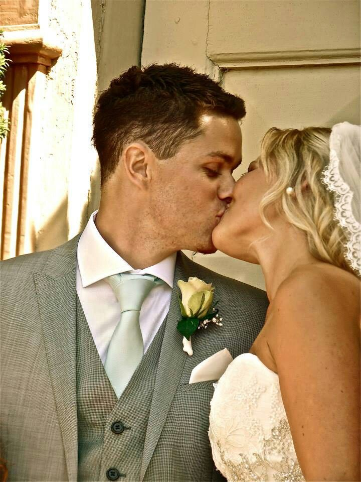 First kiss as husband and wife:-) ( groom attire,tie, boutonniere, grey suit)