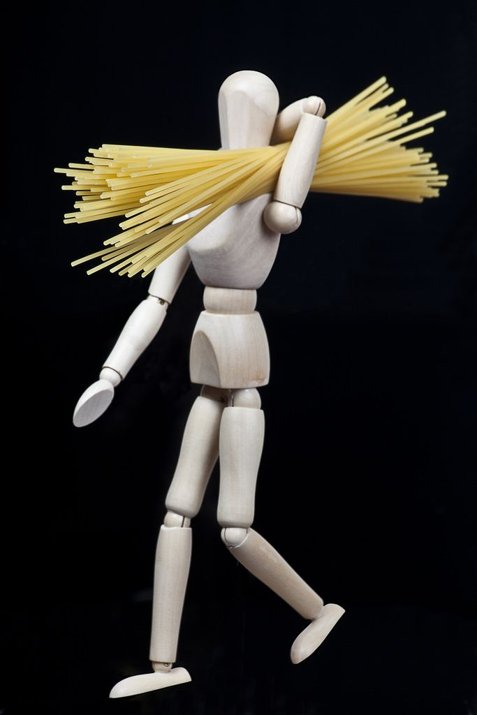 wooden model figure walking with spaghetti on his shoulder