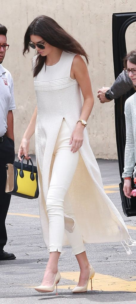 Kendall Jenner worked her longline slitted sweater with cream high-waisted pants, neutral pumps, and a gold watch. She chose a colorblock tricolor Céline bag as her statement accessory.