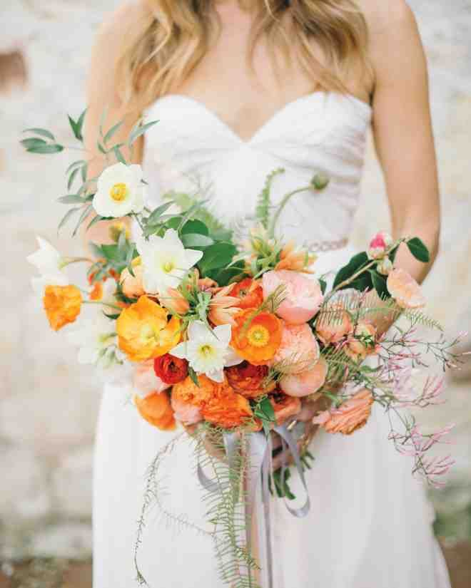 Carlie carried Icelandic poppies, daffodils, ranunculus, camellias, jasmine, ferns, and ruscus in shades of peach and white.
