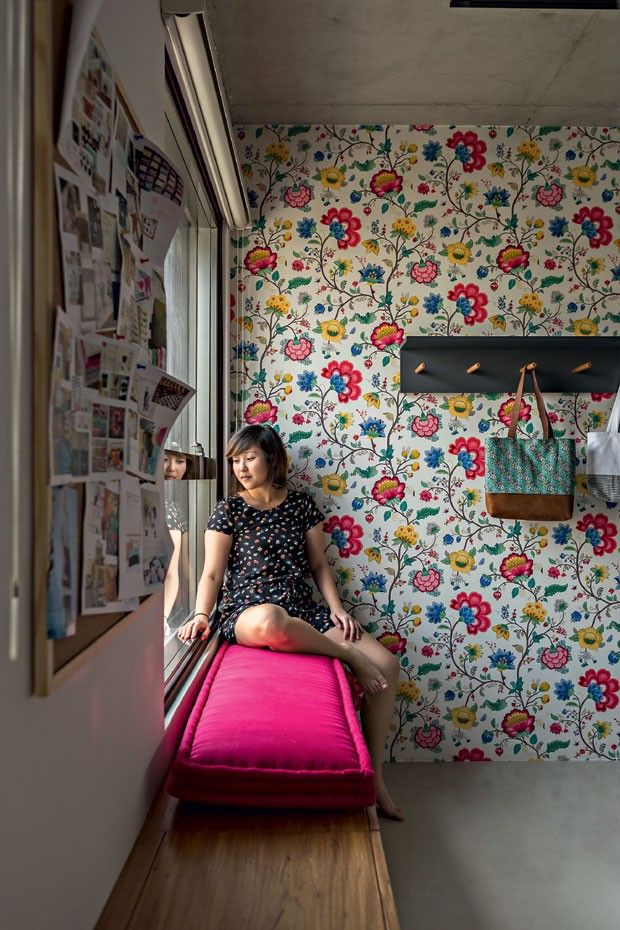 Sala de estar | No banco de freijó natural, a moradora Alina Oki está sentada sobre futon feito sob medida com tecido da Orlean. Comprado na mesma loja, o modelo floral do papel de parede da PiP Studio determinou as cores utilizadas em todo o projeto (Foto: Edu Castello/Editora Globo)