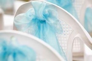 Cadeiras decoradas transformam o ambiente da festa de casamento.