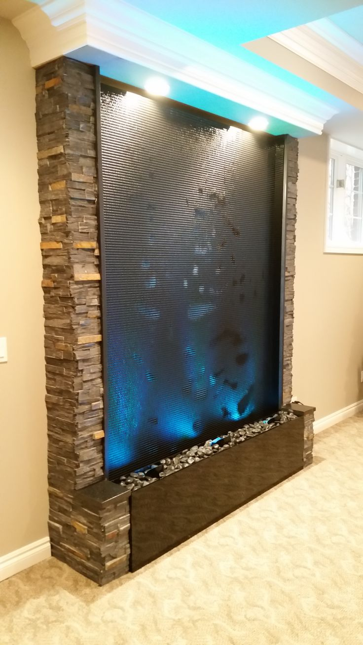 All acrylic water wall with scored face. This feature stands 8' tall and 5' wide. This also feature color changing LED lighting. Pondering Waters installed this for a residential client in Northville, MI. www.indoorwaterfalldesign.com