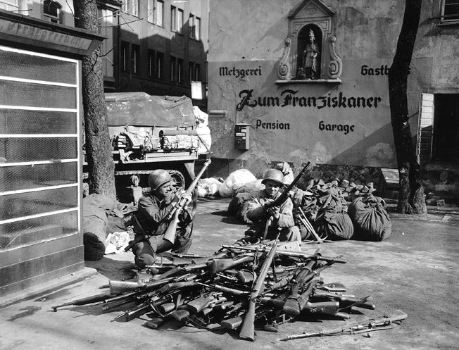 Captured German rifles taken by the 11th Armored Division are examined by American soldiers