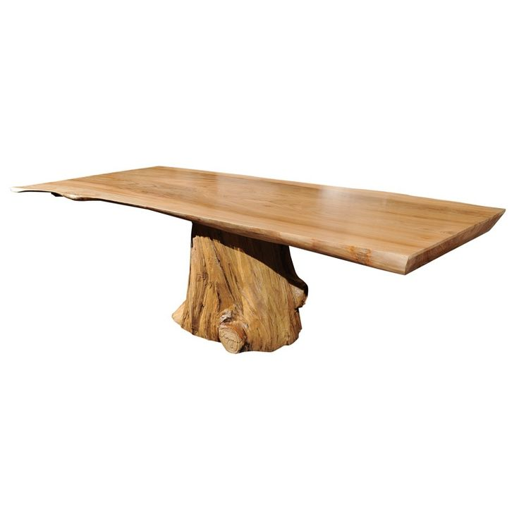 a stunning dining table made of a hand carved elm top resting on a found tree