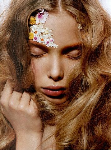 Flower child with soft pretty petals pressed against her face. Love her wispy hair and soft makeup.