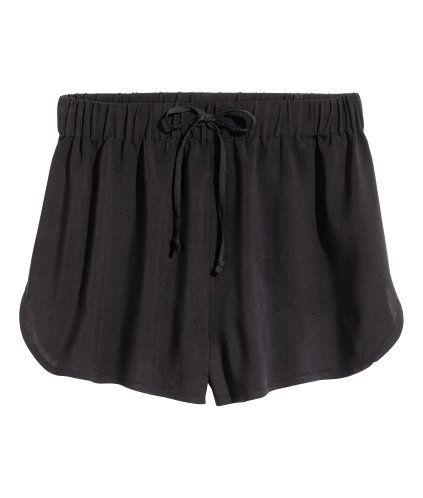 Svart. Ett par korta shorts i vävd kvalitet. De har resår och dragsko i midjan samt kort sprund i sidorna.