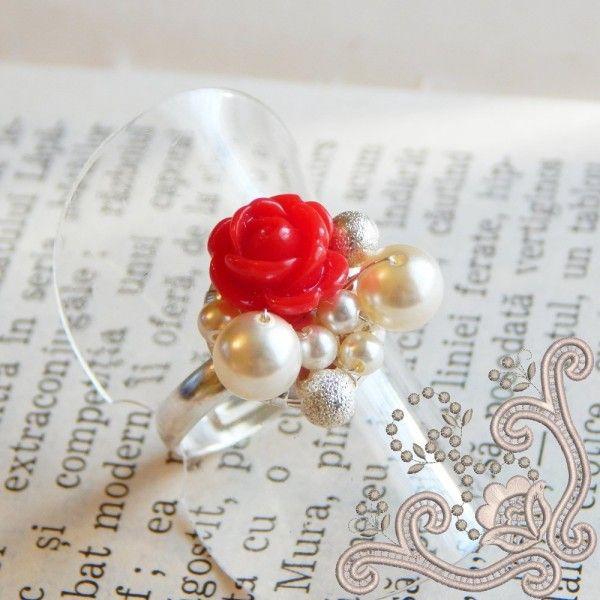 Realizat cu perle Swarovski, in combinatie cu un trandafiras polimeric de culoare rosie, acest inel iese in evidenta prin unicitatea designului. Elemente delicate, tesute cu fir subtire placat cu argint, pe o baza placata cu argint, o combinatie indrazneata si totusi elegenta. O bijuterie perfecta pentru a oferi tinutei tale un stil unic.