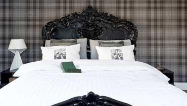 La tête de lit a l'avantage de se faire déco en donnant une seconde vie aux objets vieillots. Confirmation dans cette chambre de style londonnien avec un vieux lit dont l'heure de gloire appartient au passé.  Repeint en noir laqué au côté d'un papier peint tartan en nuances de gris vert, d'une literie et lampe de chevet d'un blanc lumière, c'est la chambre cocooning version british.