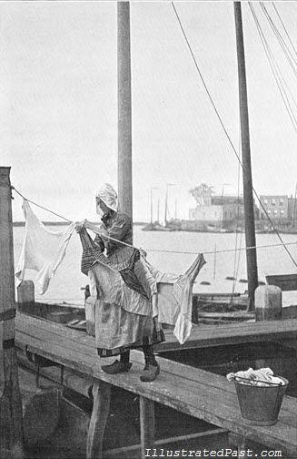 Nederlandse wasvrouw hangt de kleren op. 1906