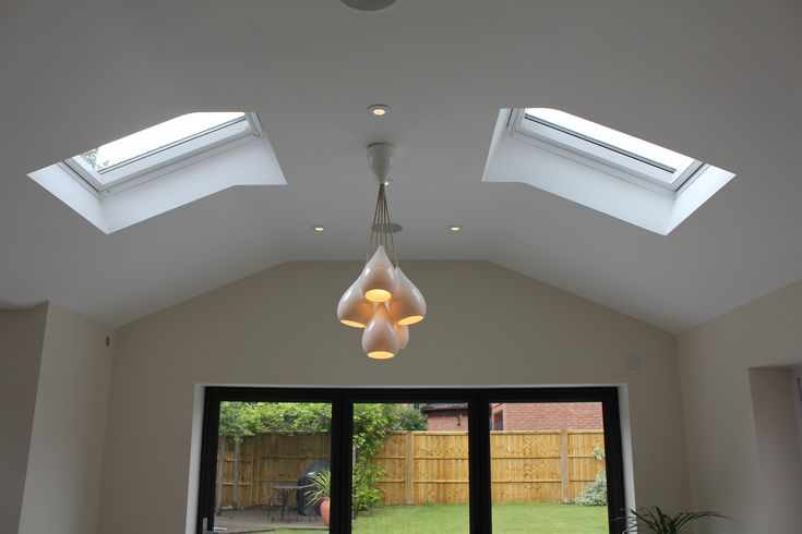 Internal view of graphite aluminium bifold doors and velux windows within roof.