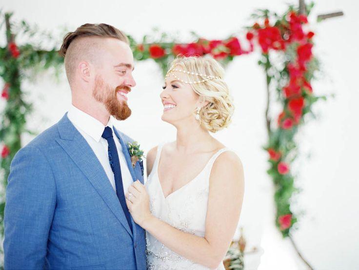 Destination wedding, Santorini, bride and groom, blue suit, floral arch