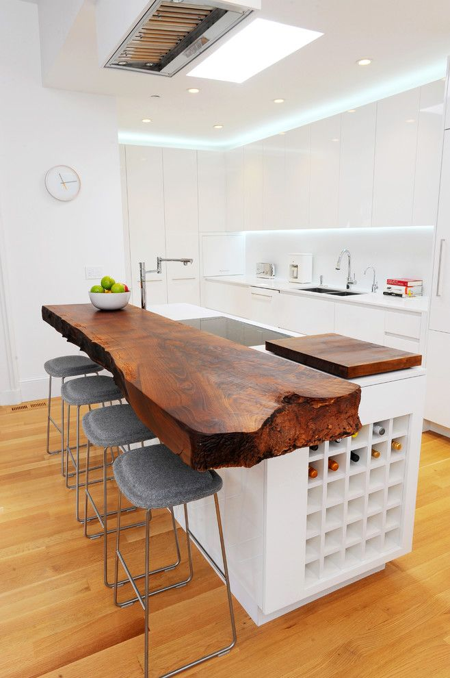 The wood slab kitchen bar counter acts as an artifact within this minimalistic kitchen