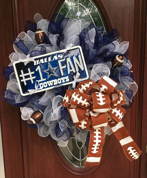 Dallas Cowboys deco mesh wreath. This wreath is perfect for any Cowboy fan out there! Its unique and there is not another one like it! The wreath is made with navy, white and gray deco mesh to match the team colors. There are 3 football embellishments throughout the wreath along with a gorgeous football ribbon bow. To make the wreath complete there is a Dallas Cowboys #1 fan license plate on it. Measurements are approximately 26 in diameter and 11 in depth. This wreath can be hung either…